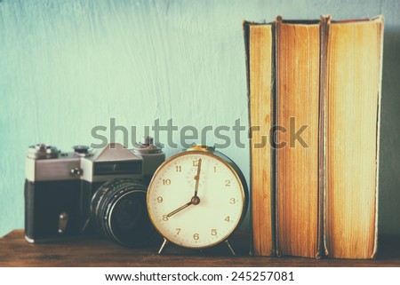 stack of books, old clock and vintage camera over wooden table. image is processed with retro faded style
