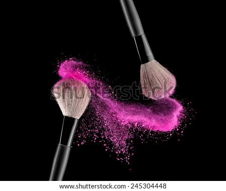 Make-up brush with pink powder explosion on black background Royalty-Free Stock Photo #245304448