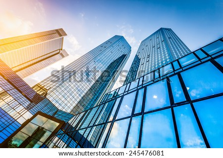 Bottom view of modern skyscrapers in business district at sunset with lens flare filter effect Royalty-Free Stock Photo #245476081