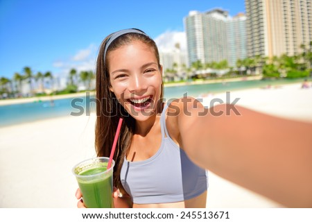 Fitness girl drinking green vegetable smoothie taking self portrait photograph with smart phone after running exercise workout on beach. Healthy lifestyle with fit Asian Caucasian woman.