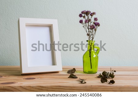 Still life with flowers and white photo frame on wooden table over grunge background, Valentine concept