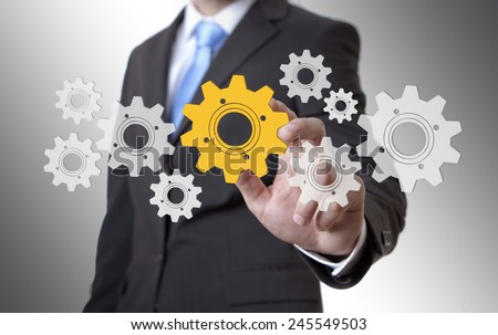Businessman playing with gears and various cogwheels #245549503