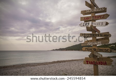 Wooden post with many written signs of different destinations in all directions, in a cloudy day,  Cala Codolar, Ibiza, Balearic Islands, Spain