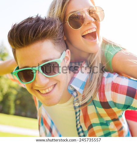 holidays, vacation, love and friendship concept - smiling teen couple in sunglasses having fun in summer park #245735557
