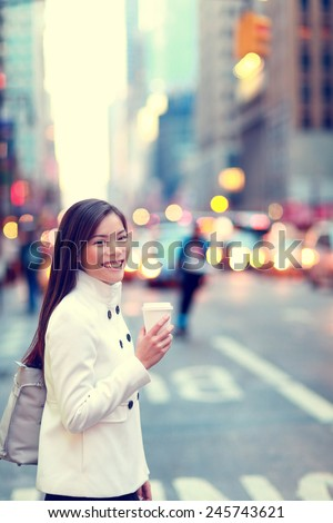 Professional young urban casual business woman in New York City Manhattan drinking coffee walking in street wearing coat downtown with yellow taxi cabs in background. #245743621