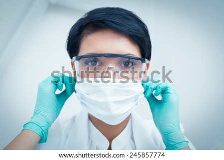 Portrait of female dentist wearing surgical mask and safety glasses #245857774