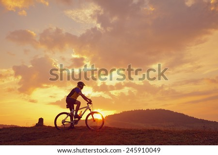 Biker and mountain bikes in the sun in front of red clouds #245910049