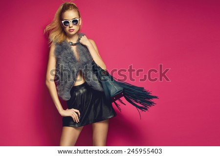Stylish beautiful blonde woman wearing feather vest holding nice big fringed handbag. Fashion picture
