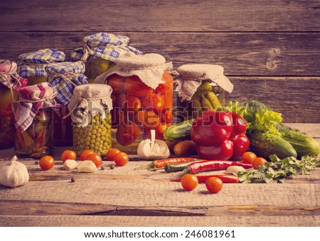 Preserved and fresh vegetables on wooden background #246081961