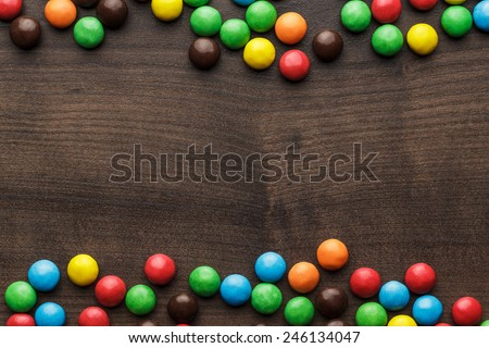 colorful sweets on the brown wooden table background