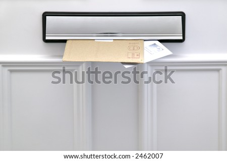 Two letters sticking out of a letterbox on a white door, space for copy #2462007