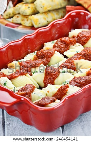 Conchigliei pasta stuffed with a ricotta, parmesan cheese and basil leaves with extreme shallow depth of field.