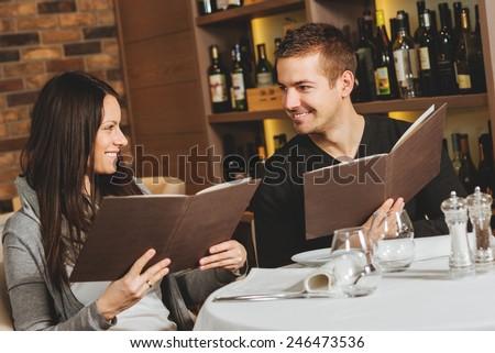 Romantic couple at a restaurant looking at the menu #246473536