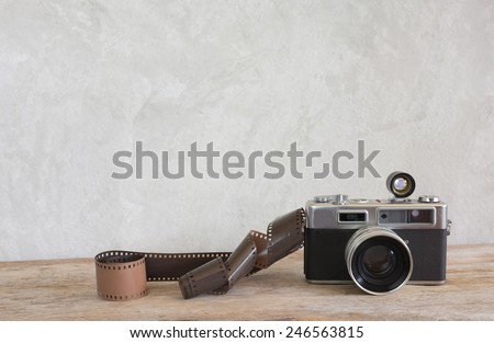 Old film camera and a roll of film on wood #246563815