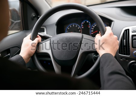 Close-up Of A Man Hands Holding Steering Wheel While Driving Car #246715444