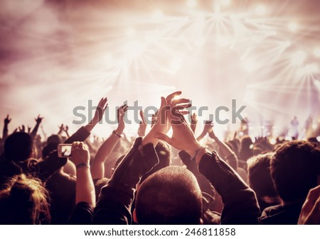 Vintage style photo of a crowd, happy people enjoying rock concert, raised up hands and clapping of pleasure, active night life concept #246811858