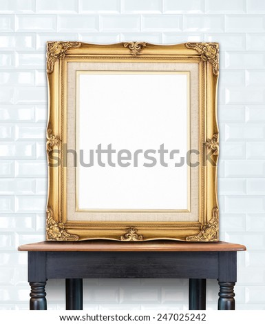 Blank vintage golden photo frame lean at white ceramic tile wall on wood table,Template Mock up for add picture. #247025242