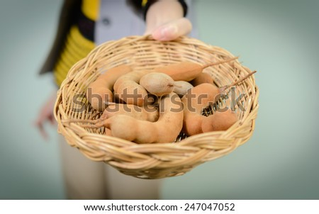 woman hold Tamarinds in wicker basket #247047052