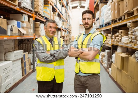 Warehouse team standing with arms crossed in a large warehouse #247101250