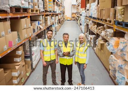 Warehouse team smiling at camera in a large warehouse #247106413