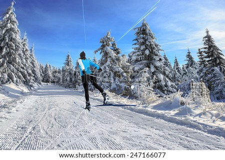A woman cross-country skiing in the Alps #247166077