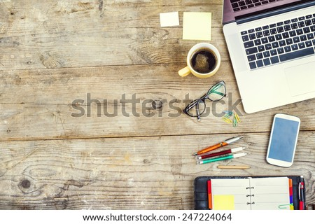 Mix of office supplies and gadgets on a wooden table background. View from above.
