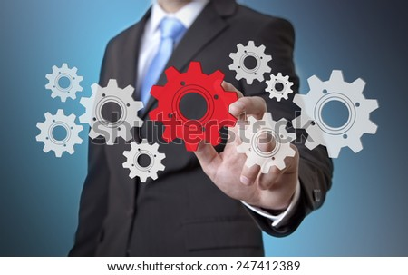 Businessman playing with gears and various cogwheels #247412389