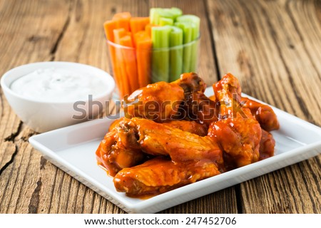 Buffalo chicken wings with cayenne pepper  sauce served hot with celery sticks and carrot sticks with blue cheese dressing for dipping Royalty-Free Stock Photo #247452706