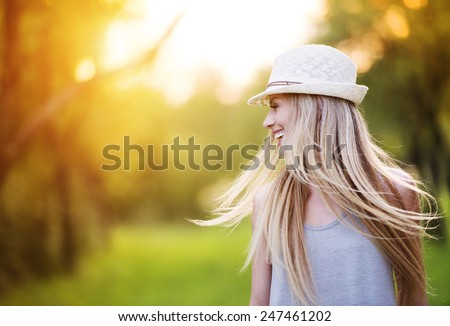 Attractive young woman enjoying her time outside in park with sunset in background. #247461202