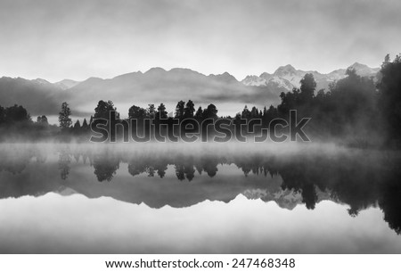 Beautiful reflections of Southern Alps at Lake Matheson, New Zealand, in the early morning mist, in black and white. #247468348