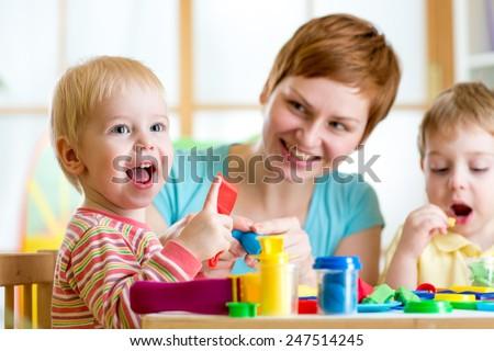 woman teaches kids handcraft at kindergarten or playschool #247514245