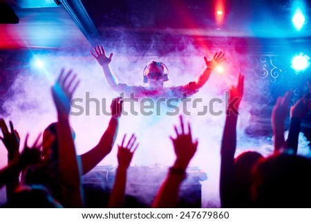 Male deejay in headphones and sunglasses looking at dancing crowd #247679860