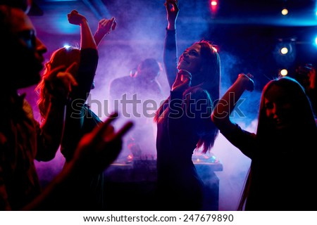 Group of dancing young people enjoying night in club Royalty-Free Stock Photo #247679890