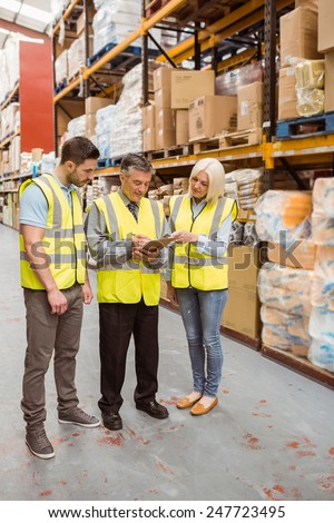 Manager writing on clipboard talking to colleague in a large warehouse #247723495