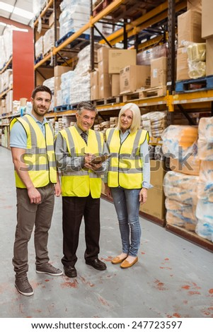 Warehouse team working together wile smiling at camera in a large warehouse #247723597