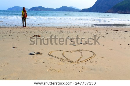 girl stand alone  after she draw two heart on the beach in valentine day