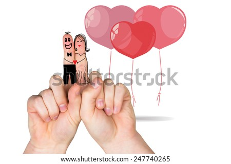 Fingers crossed like a couple against heart balloons #247740265