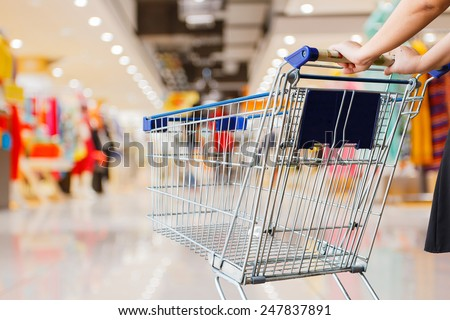 woman pushing shopping cart in shopping mall Royalty-Free Stock Photo #247837891