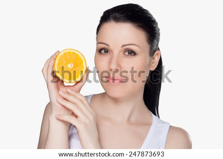 Beautiful close-up portrait of young woman with oranges. Healthy food concept. Skin care and beauty. Vitamins and minerals. #247873693