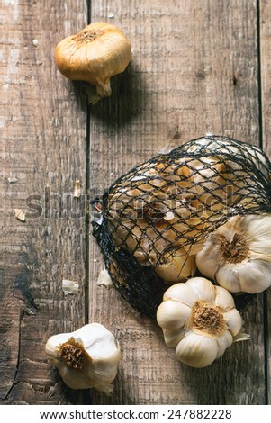 Mesh bag of smoked garlic over wooden background. Top view. See series #247882228