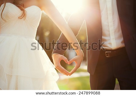 bride and groom holding hands in the shape of heart Royalty-Free Stock Photo #247899088