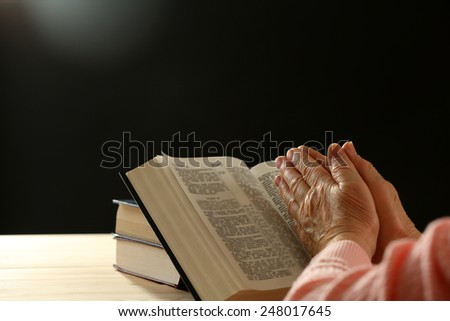 Hands of old woman with Bible on table and dark background #248017645