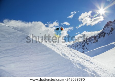 Skier skiing downhill in high mountains during sunny day. #248059390