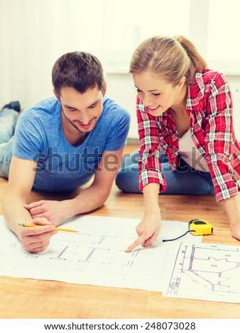 repair, building, renovation and home concept - smiling couple looking at blueprint at home #248073028