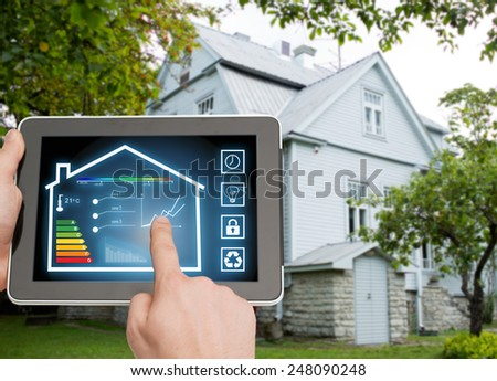 home, housing, people and technology concept - close up of man hands pointing finger to tablet pc computer and regulating room temperature over house background #248090248