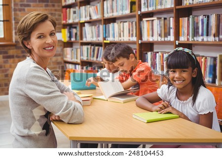 Cute pupils and teacher reading in library at the elementary school #248104453