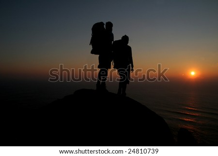 Hikers standing on rock overlooking an ocean at sunset #24810739