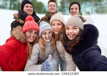 winter, technology, friendship and people concept - group of smiling men and women taking selfie and showing thumbs up outdoors #248222389