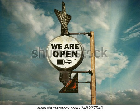 aged and worn vintage photo of we are open sign