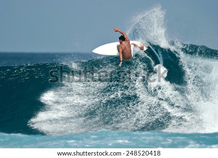 A surfer carves a radical off-the-lip. Royalty-Free Stock Photo #248520418